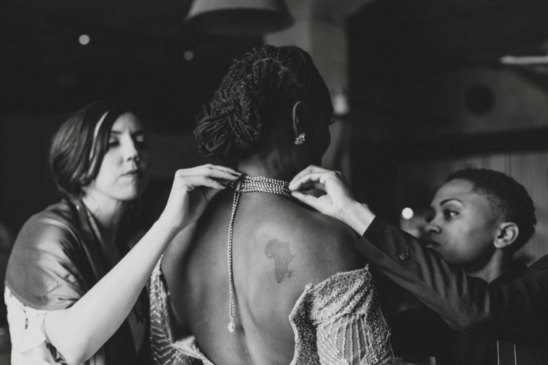 Women assist a bride as she puts on her wedding jewelry