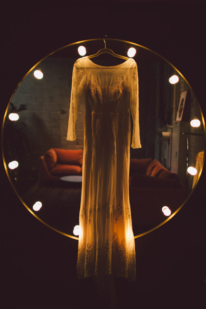 A wedding dress hangs in front of a mirror