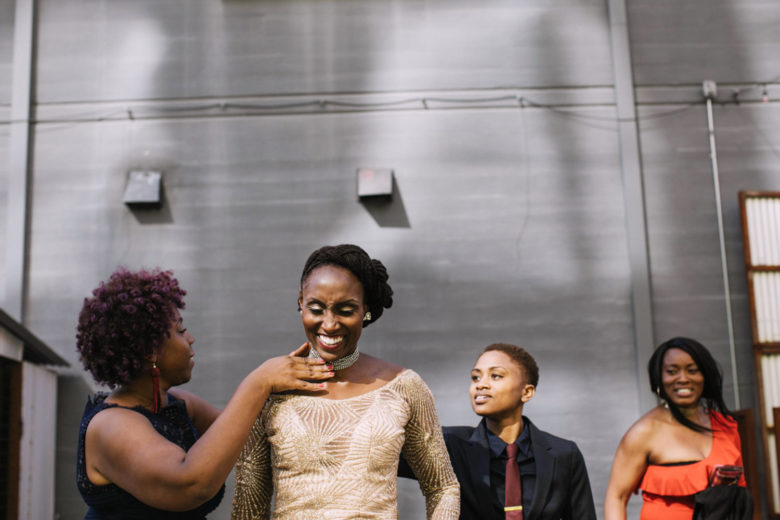 A bride smiles as her wedding party adjust her outfit with final touches