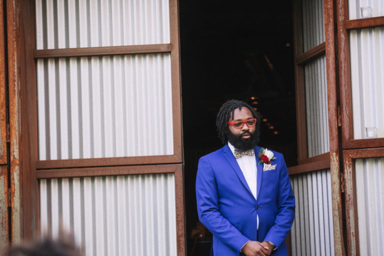 A groom nervously awaits his bride walking down the aisle