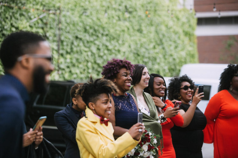 Wedding guests at a ceremony cheer on the couple with big smiles