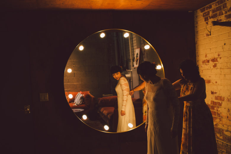 A bride stands beside a mirror as her wedding dress is zipped up from behind