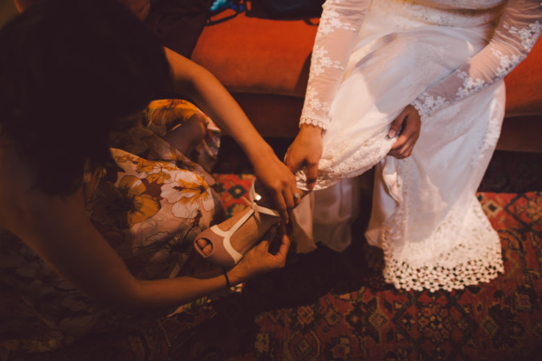 Closeup of a bride getting her shoes put on