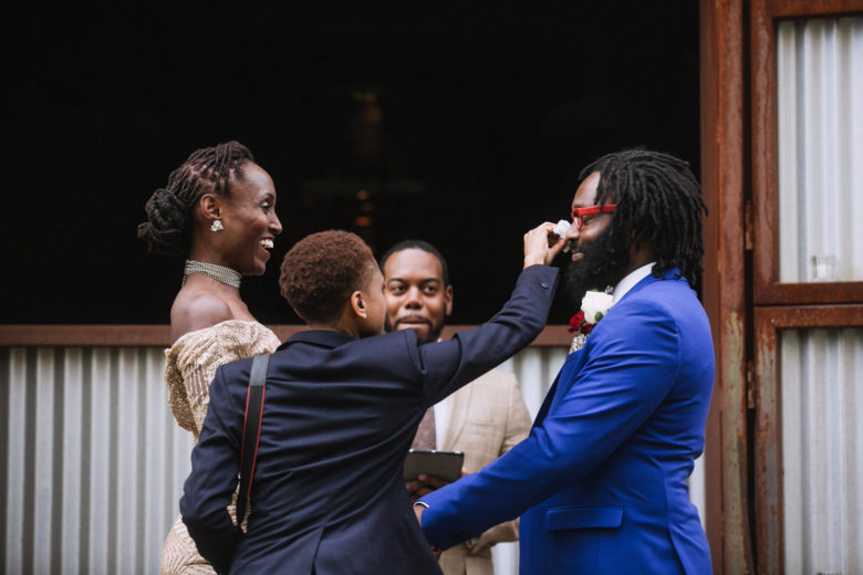 A wedding guests helpfully walks up to the groom during the ceremony to gently wipe away his tears of joy