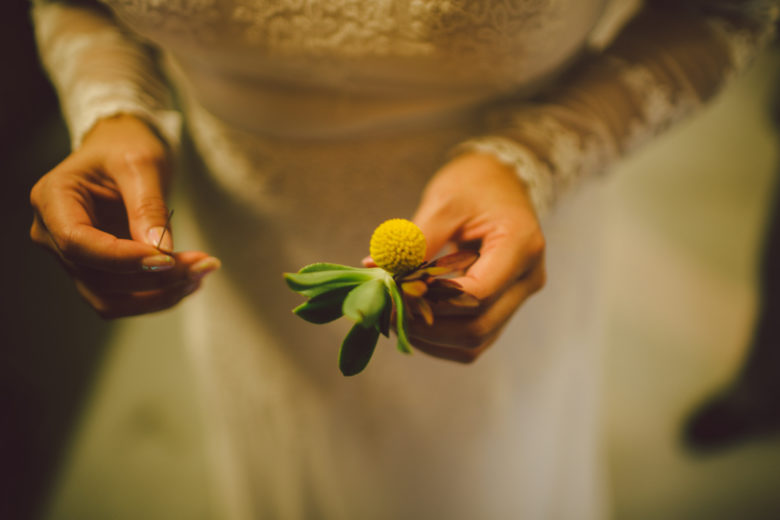 Close up of a bride holding her groom's boutonniere