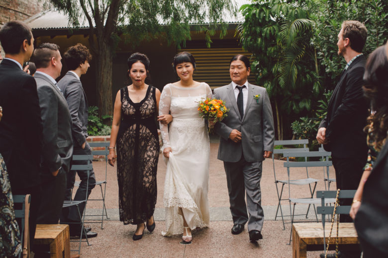 A bride is walked down the aisle by both of her parents