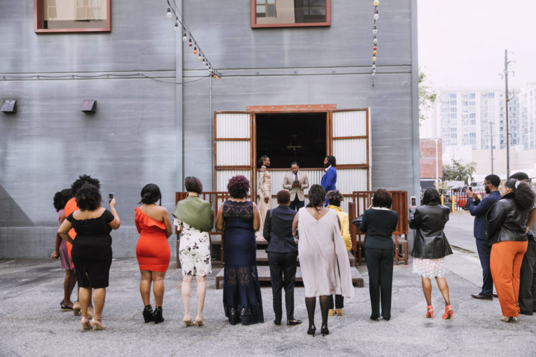 Wide view from the back of a wedding ceremony, the couple surrounded by their guests