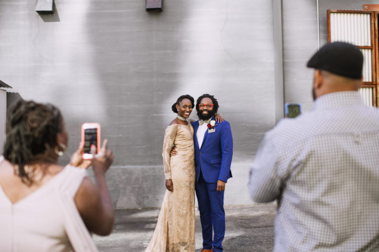 Guests at a wedding are taking photos of the couple with their cell phones