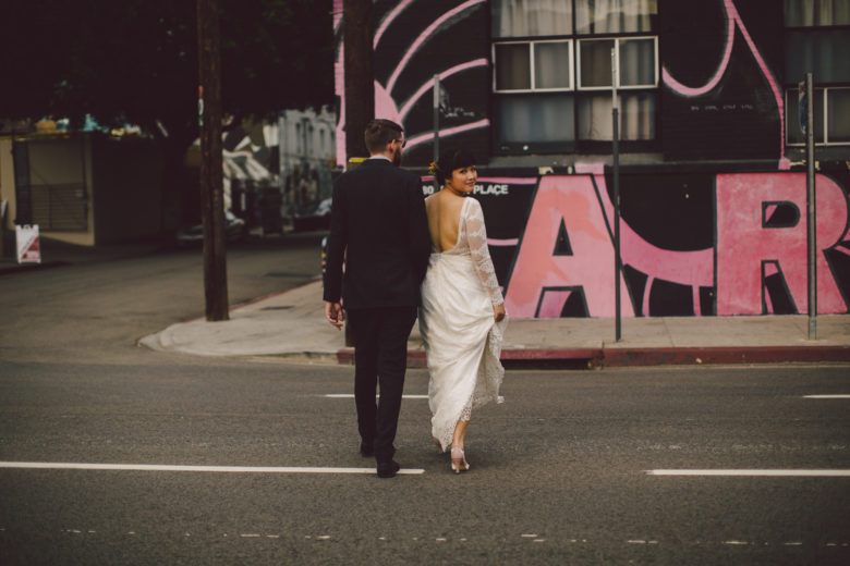 the wedding couple cross a city street as she looks over her shoulder back at the camera