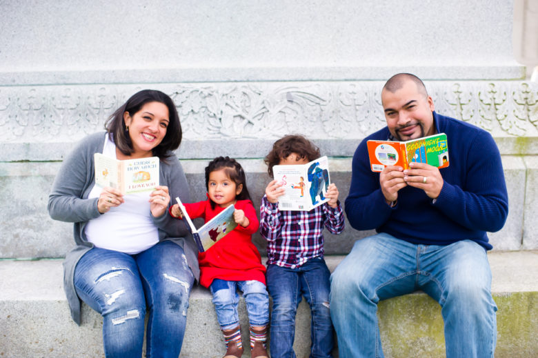 family of four reads board books on a marble step