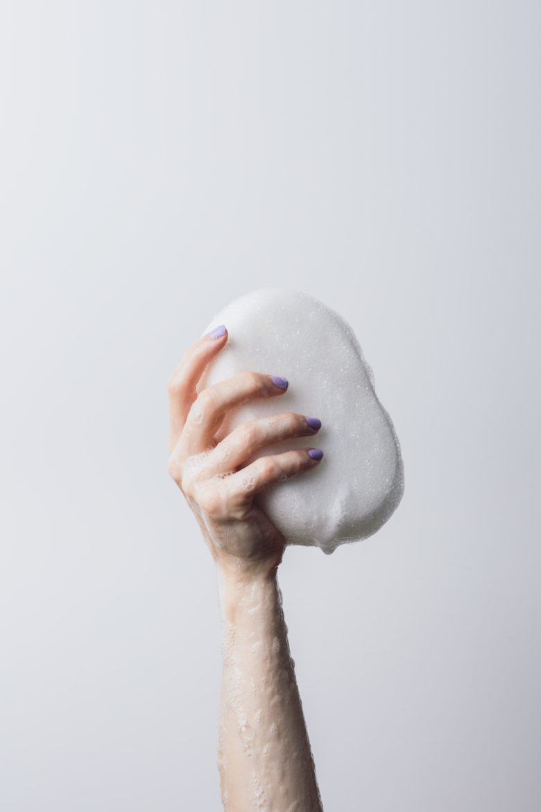 arm holding up bar of soap with lather on arm