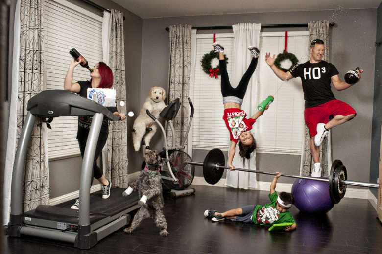 family portrait with woman on treadmill drinking wine from the bottle and eating powdered sugar mini donuts, which are falling out of the bag to an awaiting grey dog; child on the ground viewing tablet holds large barbell overhead, another child does a one-handed handstand on the barbell and shoots man with water from water bottle; man balances in tree pose on a yoga ball while holding an open beer growler, turning his head to avoid the squirt from the water bottle; white furry dog sits on a fan treadmill in the corner