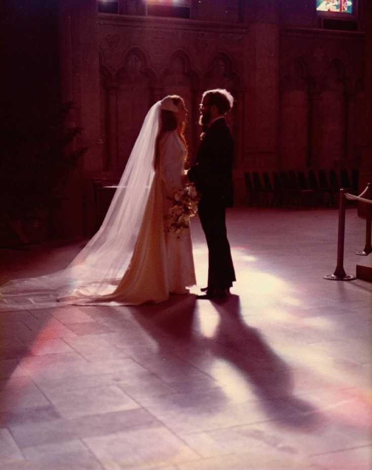 A wedding couple stand quietly in a church