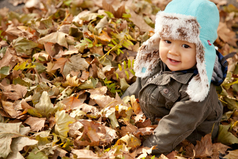 young child in a blue and fur flap cap sits in a pile of leaves, smiling