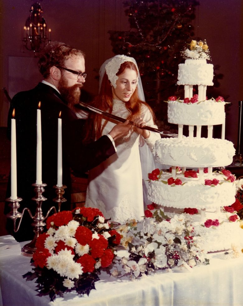 a couple cutting their wedding cake with a sabre