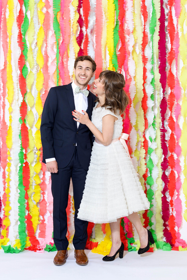 Bride and groom standing in front of a fringe streamer background wedding decoration.