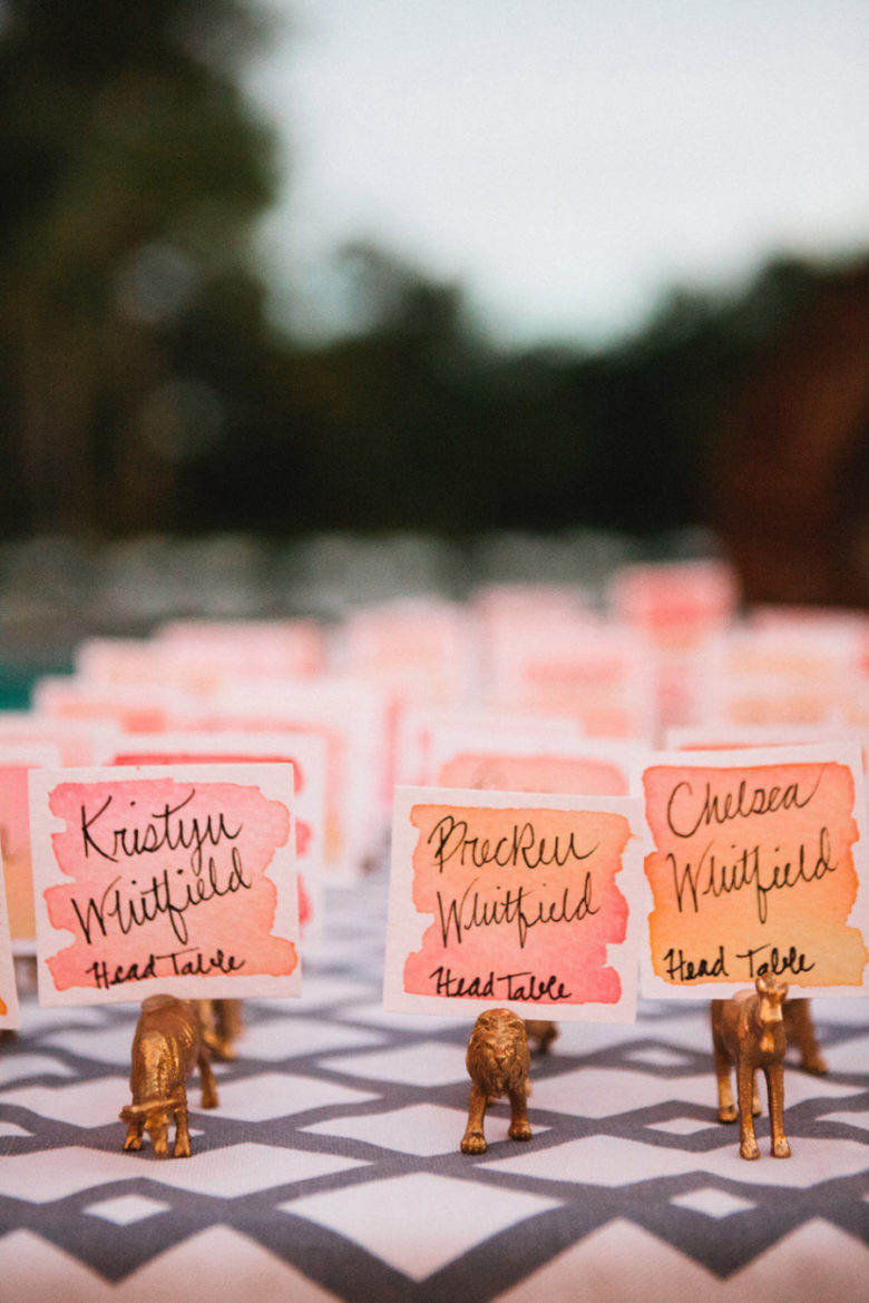 Ombre watercolor place cards in gold plastic animal holders.