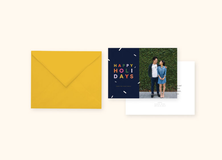holiday card stationery suite with picture of couple gazing at each other in front of green ivy-covered wall