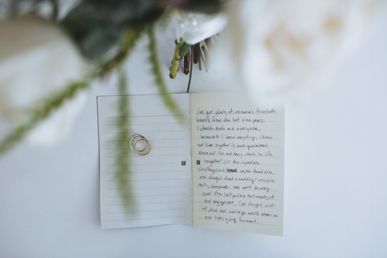 handwritten vows on small lined note pages, with wedding bands and a bouquet