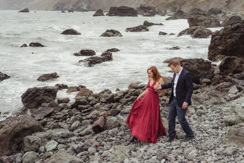 woman in red gown holds hands with man in jacket on a rocky shoreline
