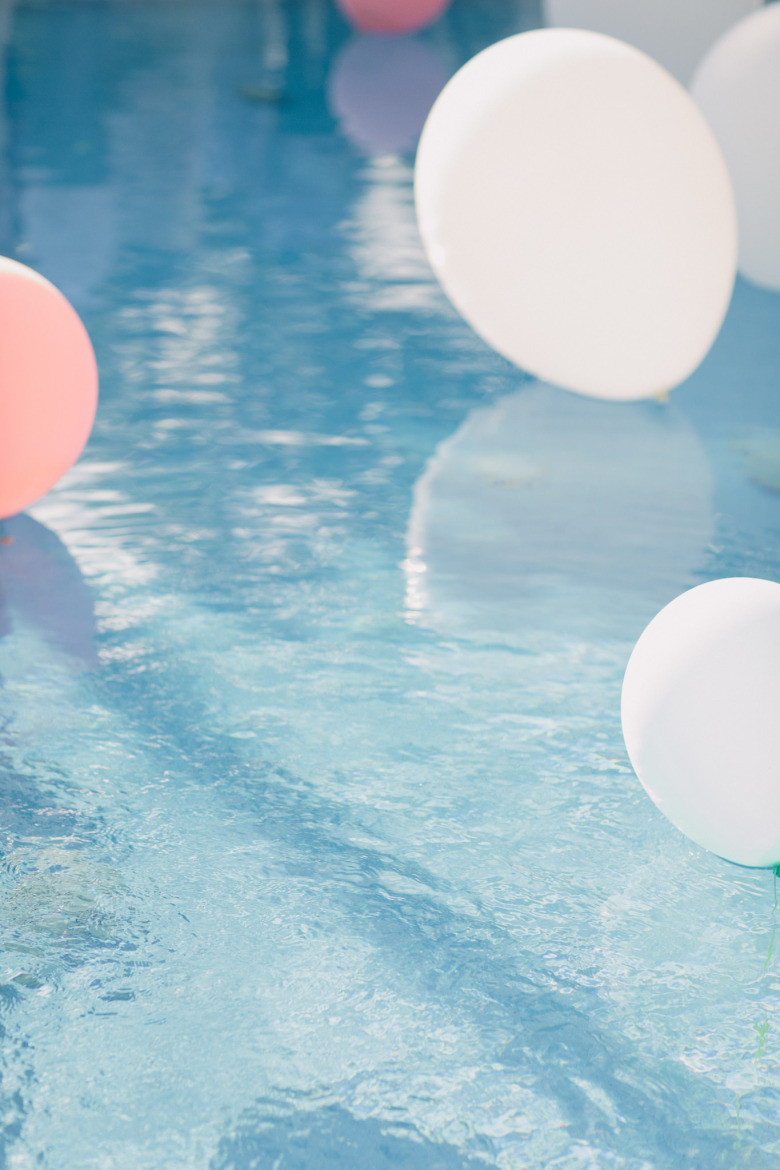 pink and white balloons floating in a swimming pool