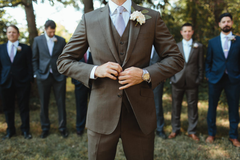 A groom buttons his suit