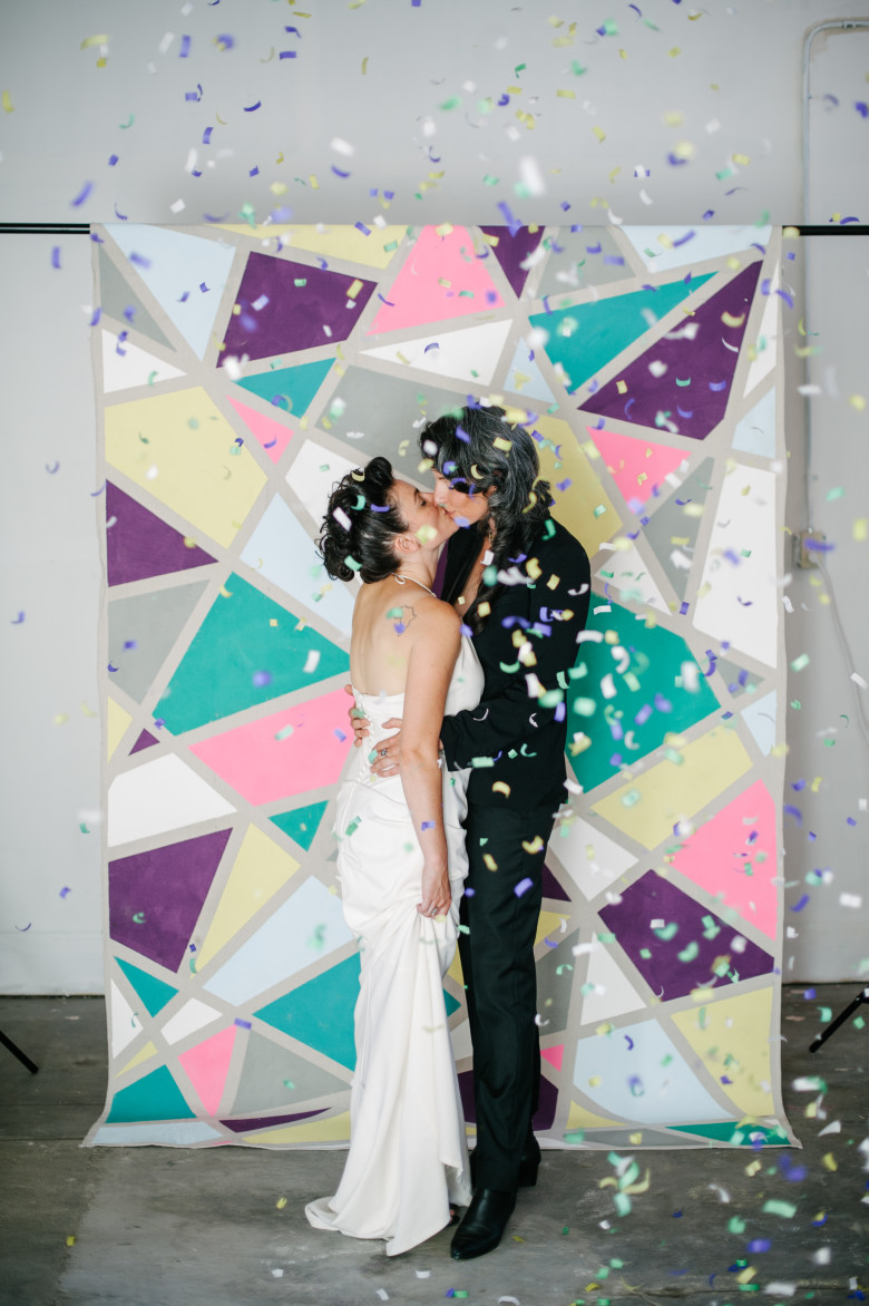 lesbian couple standing in front of a diy painted backdrop with confetti falling
