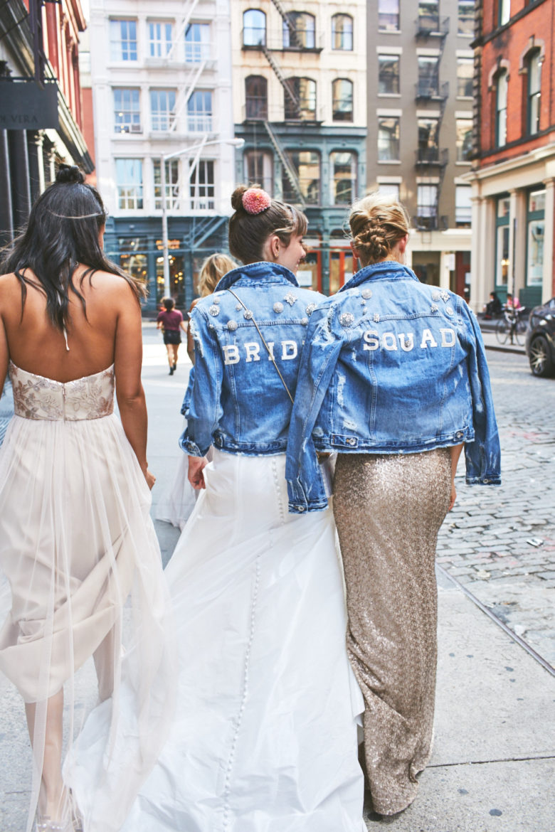 Bridesmaids and bride walking together on city streets wearing denim jackets over their dresses with the words BRIDE and SQUAD on the back.