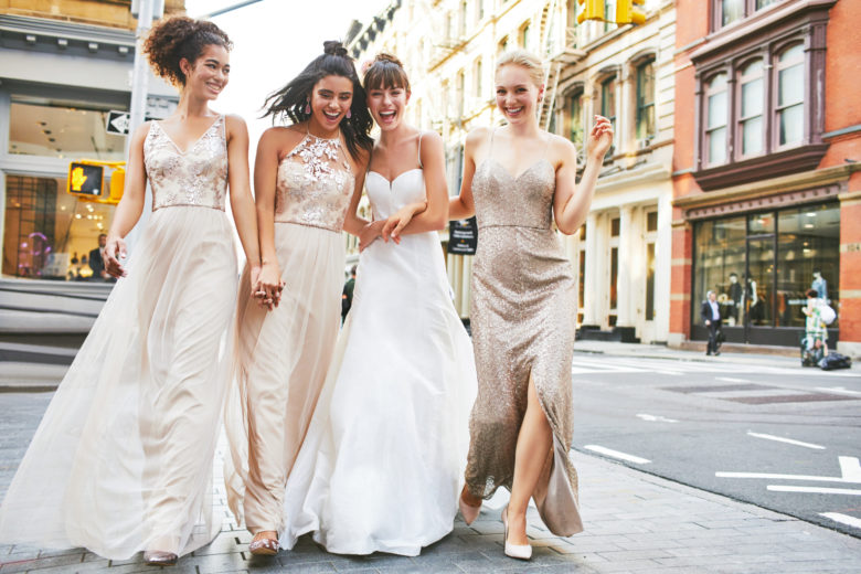 Bride and bridesmaids walking together on city streets.