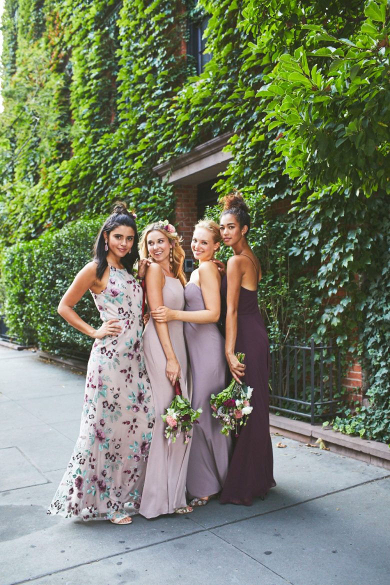 Group of bridesmaids wearing mismatched dresses in a floral and purple color palette against an ivy covered wall.