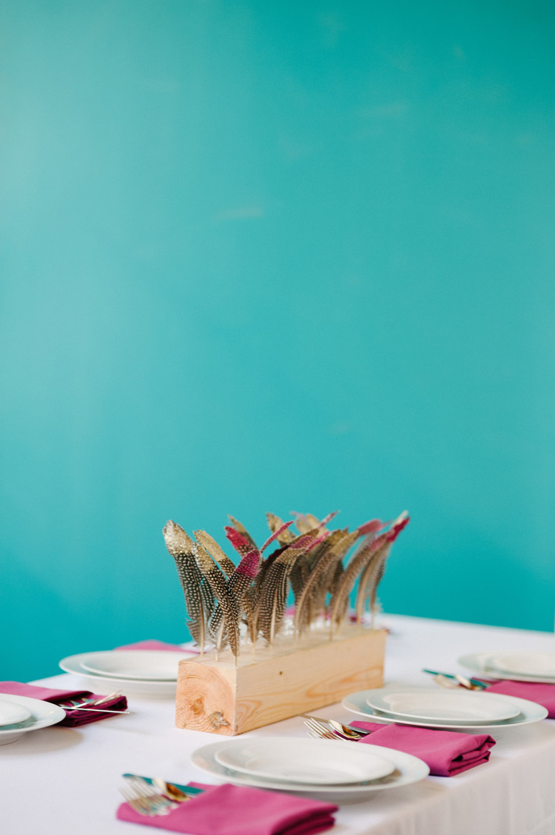 diy wood block wedding centerpiece with painted gold feathers and hot pink napkins in front of a teal wall