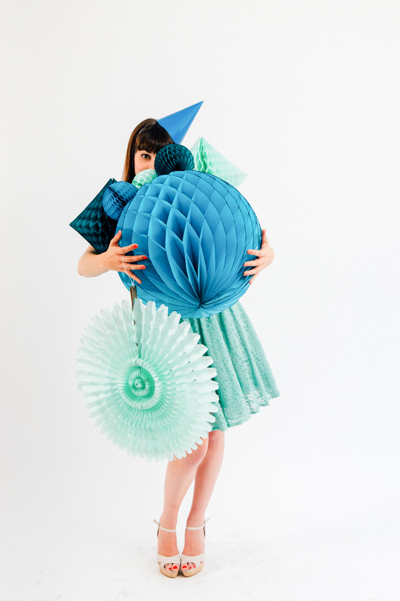 woman carrying blue tissue paper honeycomb balls and pinwheels wearing a blue party hat