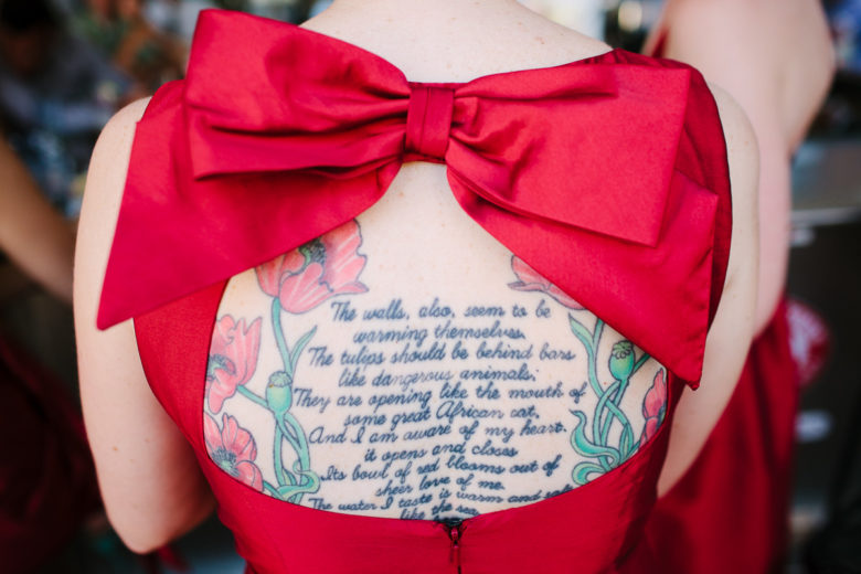 a woman's back full of tattoos seen through the window of a dress