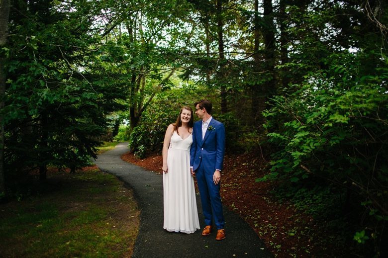 couple in wedding attire stand on small paved path in a wooded park