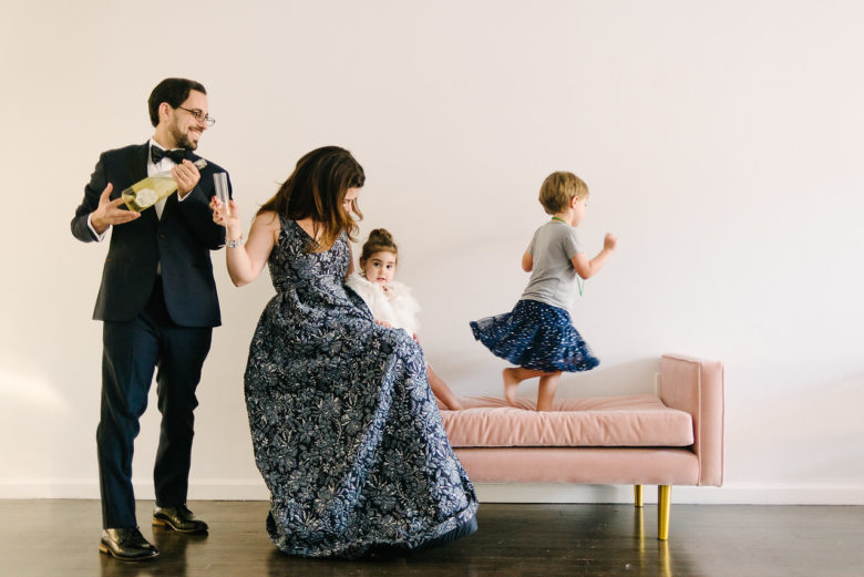 children running on a couch while parents prepare wine