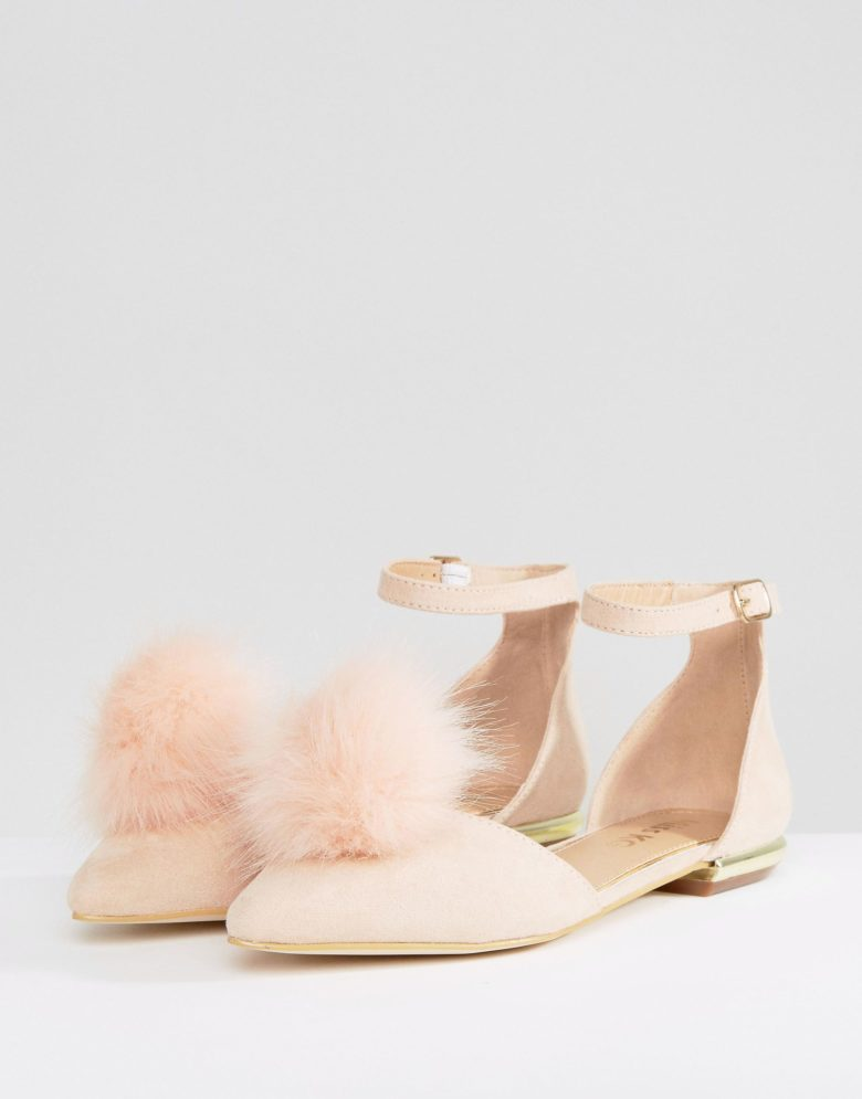 a pair of flats with a peach/pink pom