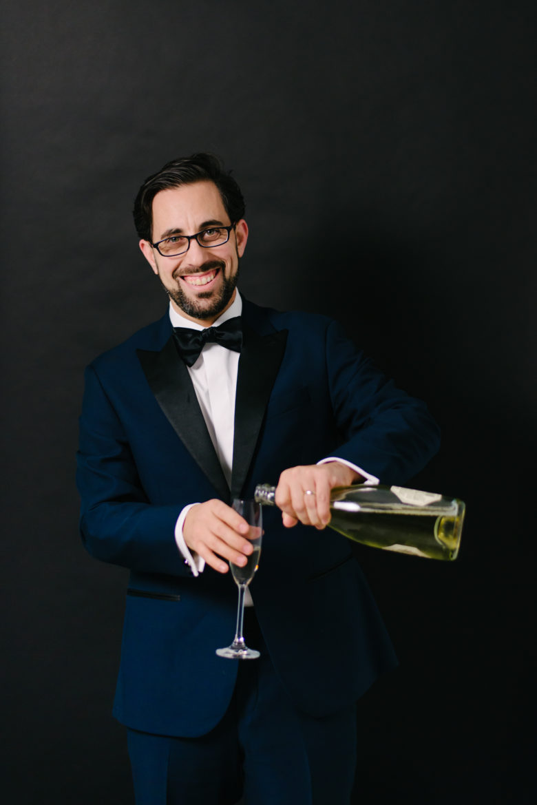 a handsome gentleman pours wine into a glass