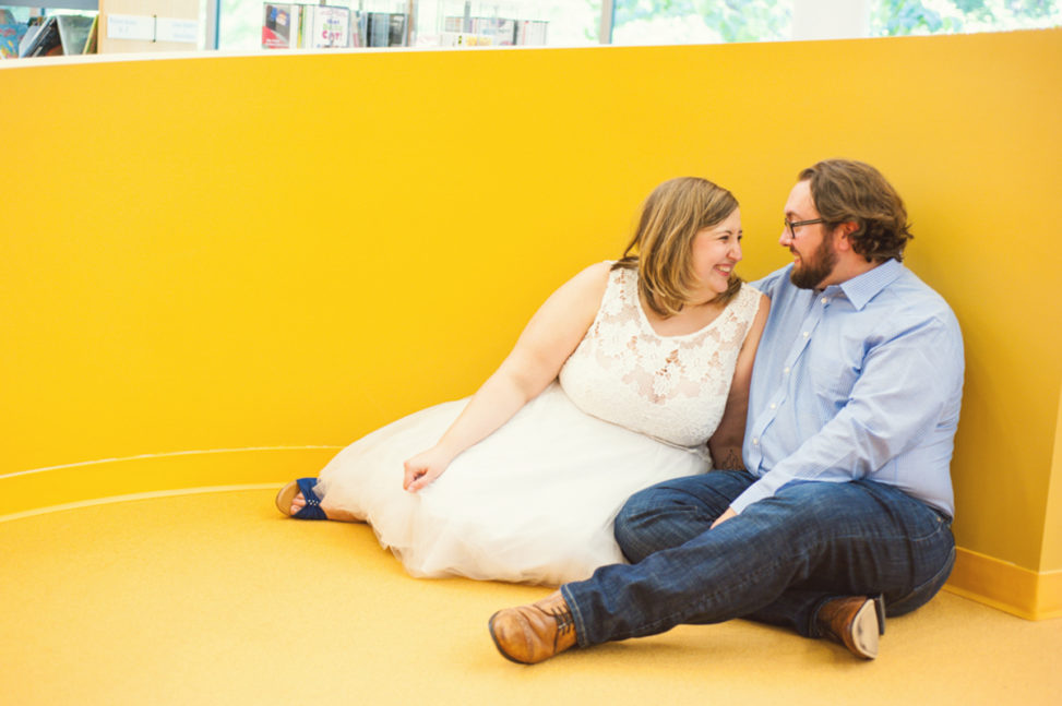 plus size white man and woman looking at each other and laughing in front of a yellow wall
