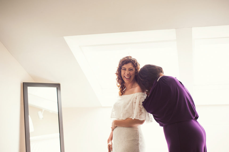 woman in off the shoulder wedding gown looking at camera and smiling while bridesmaid buries her head laughing