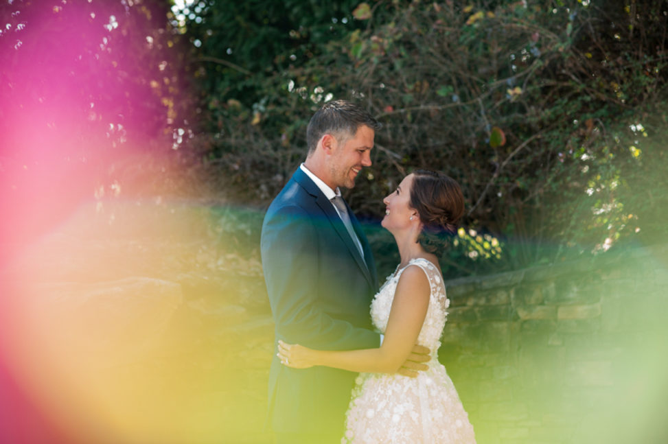 bride and groom embracing and smiling with colorful lens flare