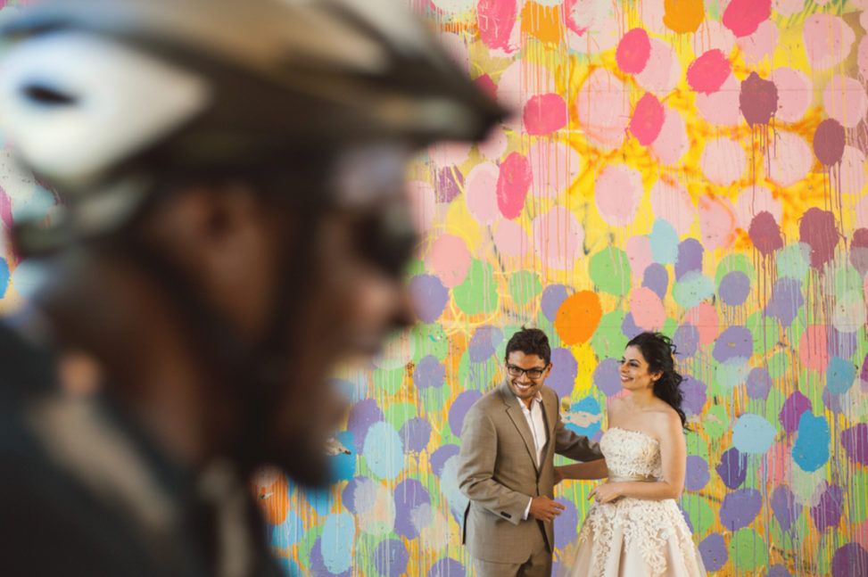 man and women standing in front of a mural wall laughing with a laughing bike messenger riding by in the foreground