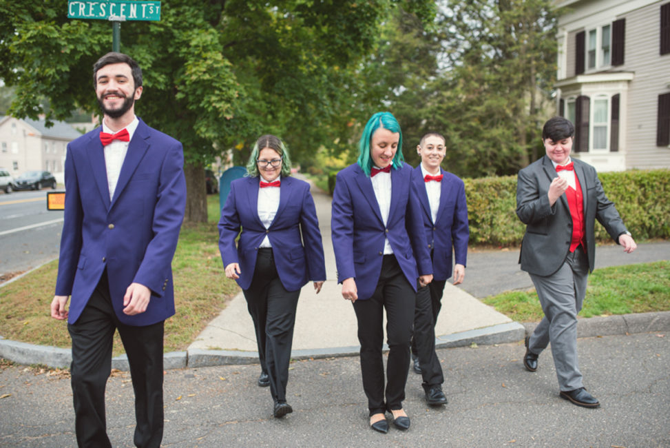 mixed gender bridal party in black pants and purple blazers crossing street