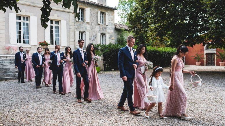 processional of bridesmaids in pink dresses and groomsmen in blue suits through gravel yard