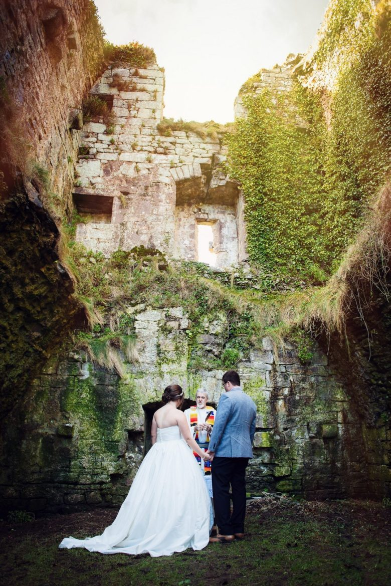 bride and groom holding hands in front of officiant in a chamber of castle ruins