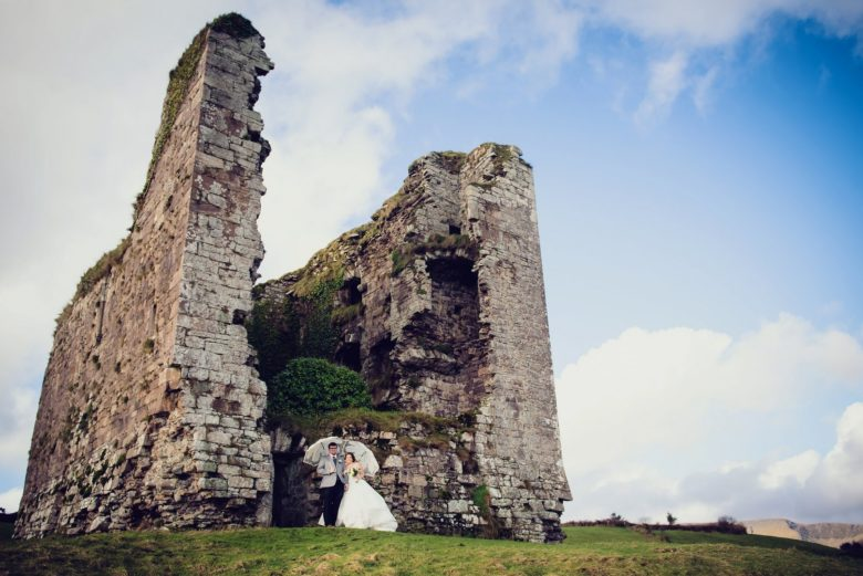 bride and groom with white umbrellas in front of castle ruins