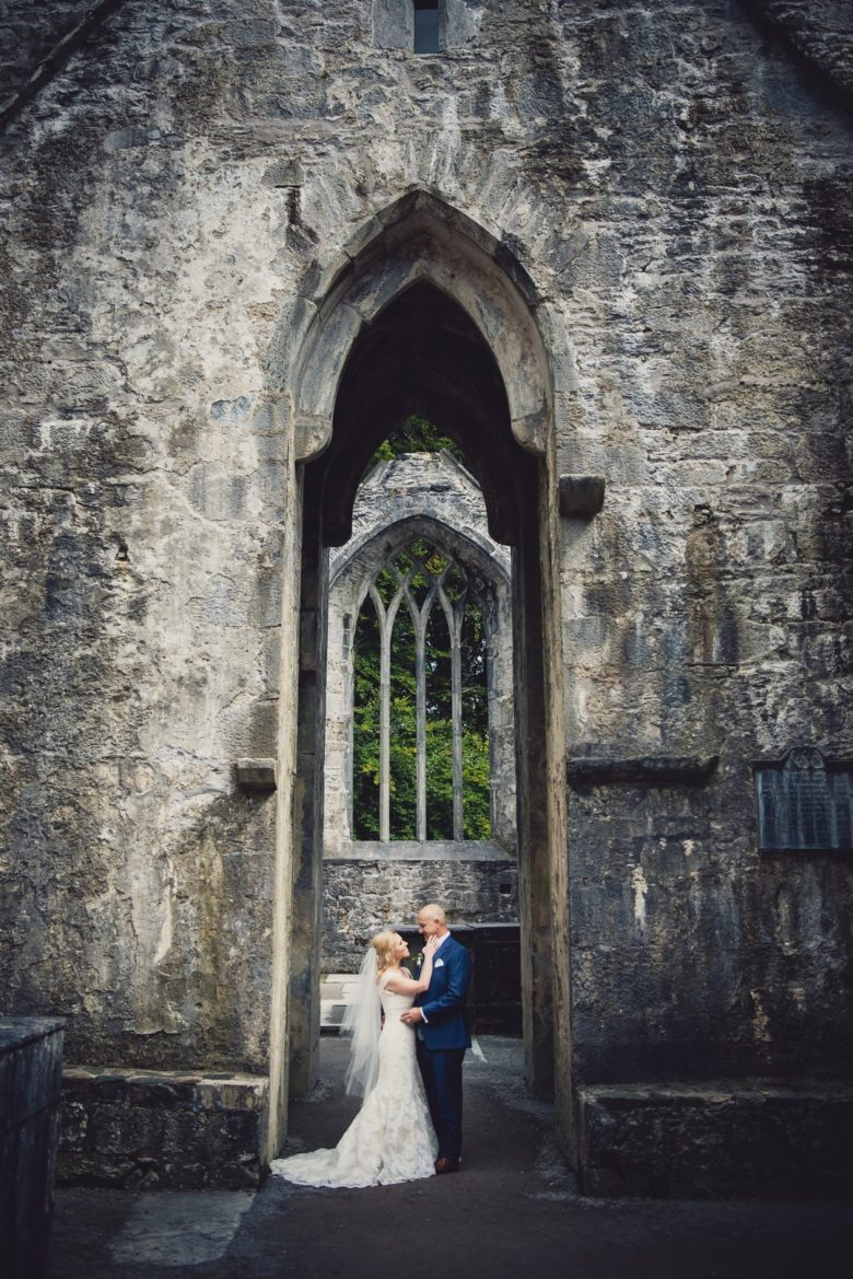 bride and groom embracing under a tall castle archway