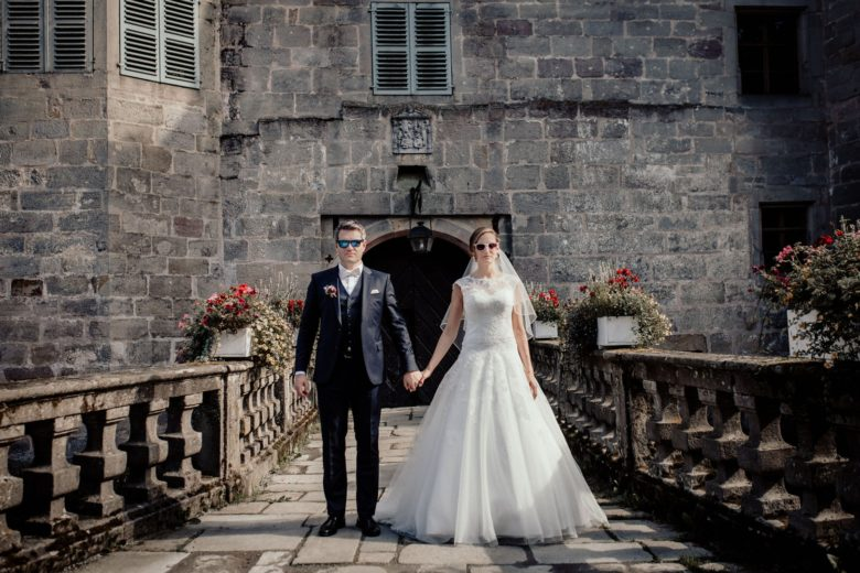 bride and groom holding hands on a bridge in front of castle