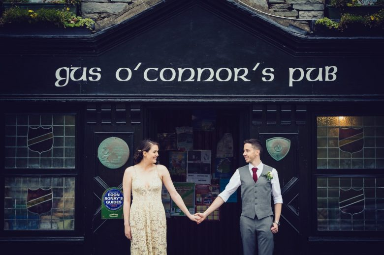 bride and groom holding hands in front of o'connor's pub