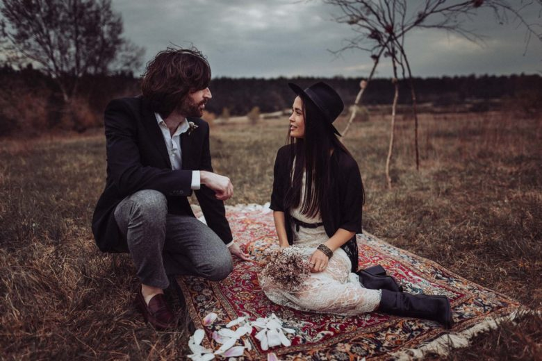 bride with black fedora and groom in jeans sitting on a picnic blanket in a field