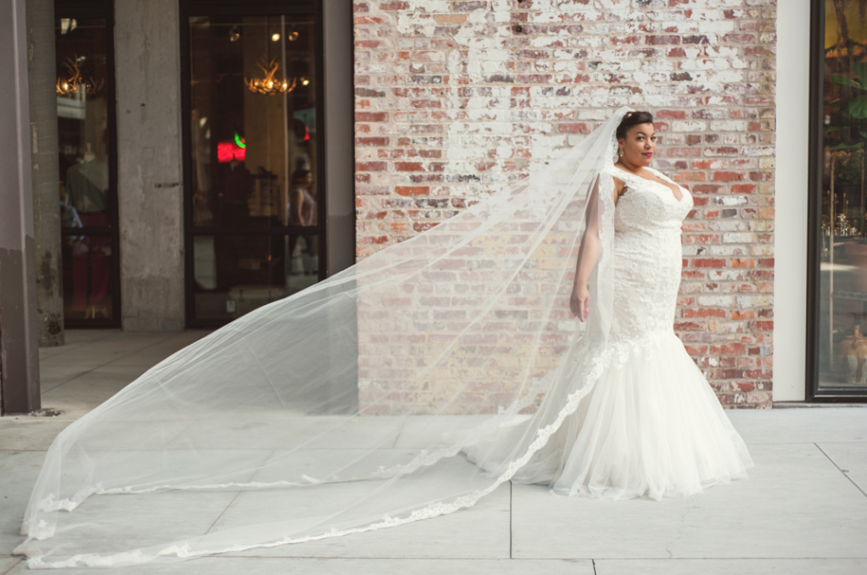 plus size black bride in front of a brick wall in a mermaid wedding gown and cathedral length veil blowing behind her